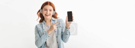 Photo for Panoramic shot of happy teenager listening music with headphones and pointing at smartphone with blank screen, isolated on white - Royalty Free Image