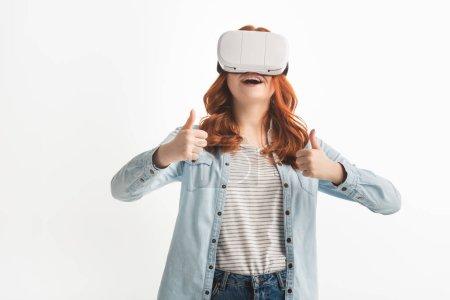 """Photo pour Un adolescent excité à la tête rouge montrant les pouces levés et utilisant un casque d """"écoute de réalité virtuelle, isolé sur blanc - image libre de droit"""