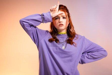 Photo pour Rousse adolescente de mauvaise humeur montrant un signe de perdant, sur violet et beige - image libre de droit