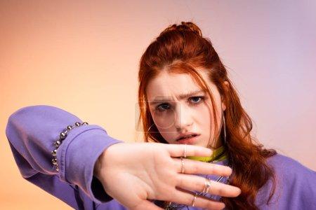 Photo pour Jeune adolescente à tête rouge de mauvaise humeur au geste d'arrêt, en violet et beige - image libre de droit