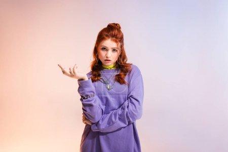 Photo pour Belle confuse rousse adolescent fille, sur violet et beige - image libre de droit
