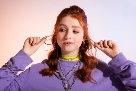 Photo for Beautiful smiling redhead teen girl holding earrings, on purple and beige - Royalty Free Image