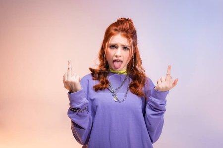 Photo pour Une adolescente à tête rouge sortant la langue et montrant les majeur, sur violet et beige - image libre de droit