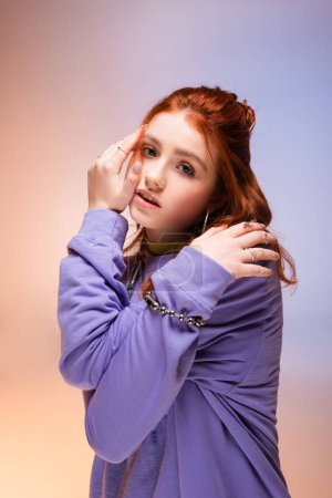 Photo for Attractive bored redhead teen girl, on purple and beige - Royalty Free Image