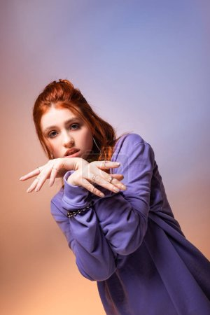 Photo for Beautiful bored redhead teen girl gesturing on purple and beige - Royalty Free Image