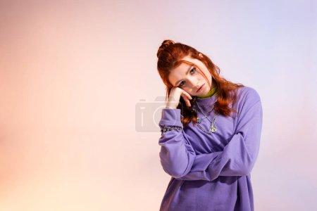 Photo pour Belle fille adolescente rousse ennuyée, sur violet et beige - image libre de droit