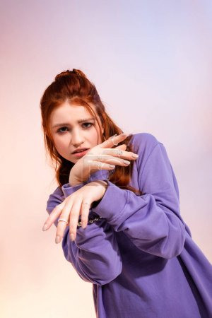 Photo for Beautiful redhead teen girl in bad mood, on purple and beige - Royalty Free Image