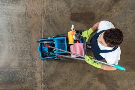 Photo pour Vue de dessus du nettoyeur en uniforme chariot transportant les produits de nettoyage - image libre de droit