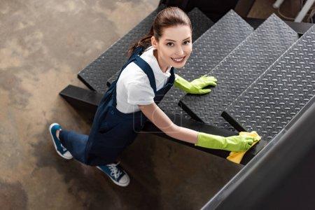 Photo pour Vue aérienne du nettoyeur souriant essuyant les escaliers et regardant la caméra - image libre de droit