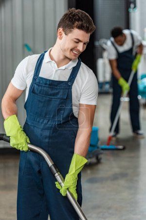 Photo for Selective focus of smiling cleaner near african american colleague washing floor with mop - Royalty Free Image