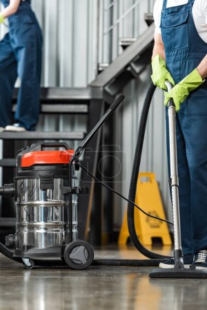cropped view of cleaner vacuuming floor near colleague cleaning stairs