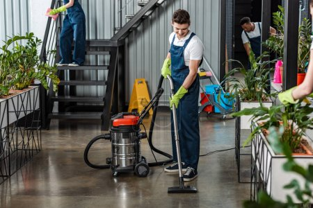 Photo for Young cleaner cleaning floor with vacuum cleaner near multicultural colleagues - Royalty Free Image