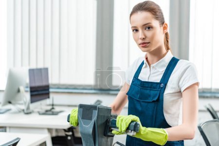 Photo for Attractive cleaner in overalls looking at camera while standing with cleaning machine - Royalty Free Image