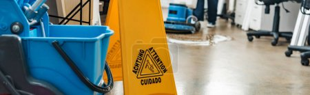 selective focus of wet floor caution sign and bucket, while cleaner washing floor with cleaning machine on backround