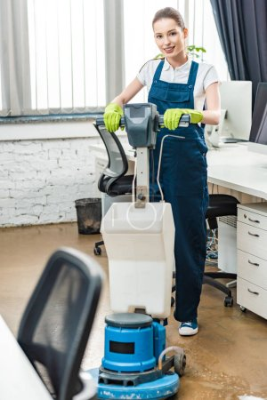 Photo for Smiling cleaner looking at camera while washing floor with cleaning machine - Royalty Free Image