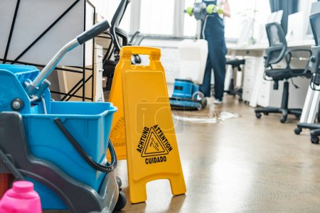 Photo for Selective focus of cart with buckets and wet floor caution sign, and cleaner washing floor with cleaning machine on background - Royalty Free Image