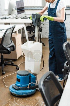 Photo pour Vue recadrée du plancher de lavage plus propre dans le bureau avec machine de nettoyage - image libre de droit