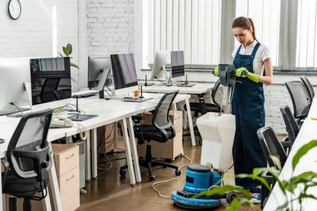 Photo for Young cleaner washing floor in open space office with cleaning machine - Royalty Free Image