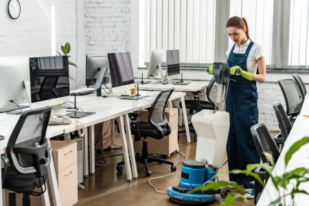 young cleaner washing floor in open space office with cleaning machine