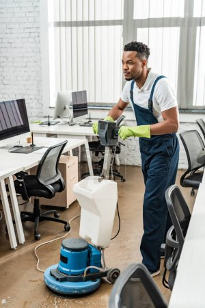 handsome african american cleaner washing floor in office with cleaning machine