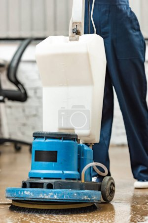 cropped view of cleaner washing floor in office with cleaning machine
