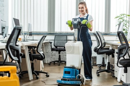 Photo pour Nettoyage souriant plancher de lavage dans le bureau avec machine de nettoyage - image libre de droit
