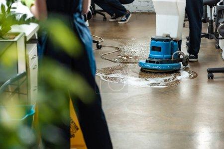 Ausgeschnittener Blick auf sauberen Waschboden mit Putzmaschine in der Nähe von Kollegen