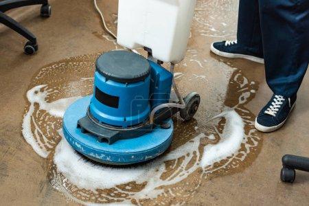 Photo pour Vue recadrée du plancher de lavage plus propre avec machine de nettoyage - image libre de droit