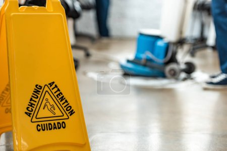 Photo for Selective focus of wet floor caution sign near cleaner washing floor with cleaning machine - Royalty Free Image