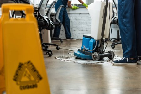 Photo for Cropped view of cleaner washing floor with cleaning machine near colleague - Royalty Free Image