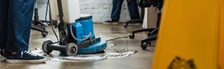 Photo pour Vue recadrée du sol nettoyant avec machine de nettoyage, vue panoramique - image libre de droit