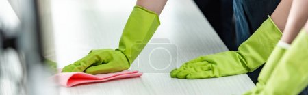 cropped view of cleaner in rubber gloves washing office desk