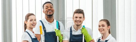 Photo for Panoramic shot of cheerful multicultural team of cleaners looking at camera while standing in office - Royalty Free Image