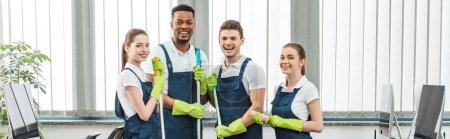 Foto de Plano panorámico de alegre equipo multicultural de limpiadores mirando a la cámara mientras están de pie en la oficina - Imagen libre de derechos