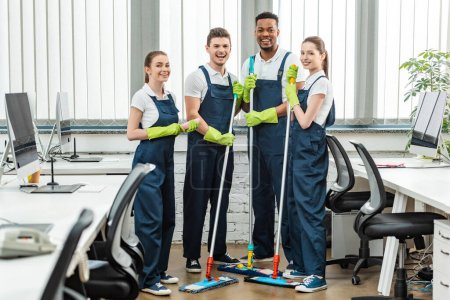 Photo for Cheerful multicultural team of cleaners looking at camera while standing with mops in office - Royalty Free Image