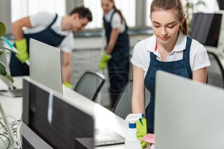 Photo for Selective focus of pretty cleaner wiping desk while colleagues cleaning floor in office - Royalty Free Image