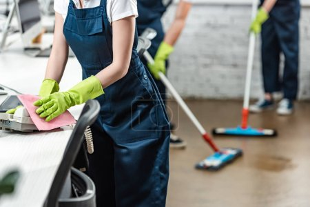 cropped view of cleaner wiping phone while colleagues washing floor with mops