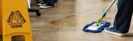 Photo pour Vue recadrée du sol nettoyant avec balai près du sol mouillé signe d'avertissement, vue panoramique - image libre de droit