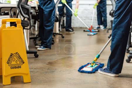 Foto de Vista recortada del equipo de limpiadores jóvenes lavando piso con fregonas en la oficina - Imagen libre de derechos