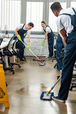 Photo pour Équipe multiculturelle de jeunes nettoyeurs lavant le sol avec des vadrouilles dans le bureau - image libre de droit