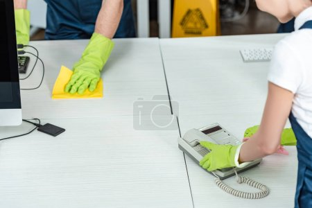 Photo for Partial view of cleaner wiping office phone near colleague washing desk - Royalty Free Image