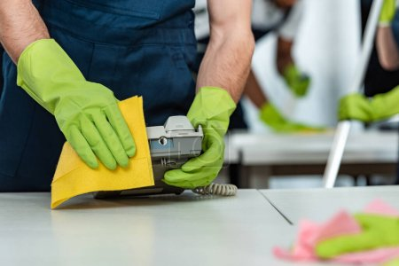 partial view of cleaner in rubber gloves cleaning office phone with rag