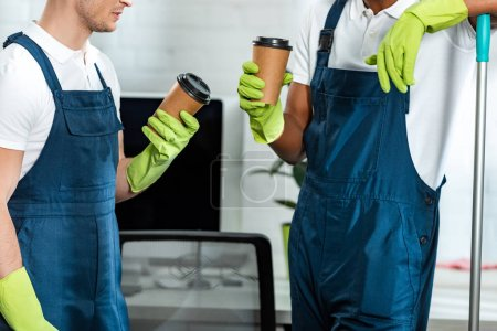 Photo for Cropped view of multicultural cleaners holding coffee to go in office - Royalty Free Image
