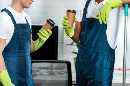Foto de Vista panorámica de los limpiadores multiculturales que tienen café para ocupar el cargo. - Imagen libre de derechos