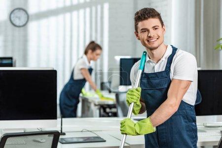 Photo pour Nettoyage souriant plancher de lavage tandis que collègue de nettoyage bureau - image libre de droit