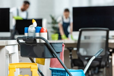 selective focus of cart with cleaning supplies and two cleaners on background