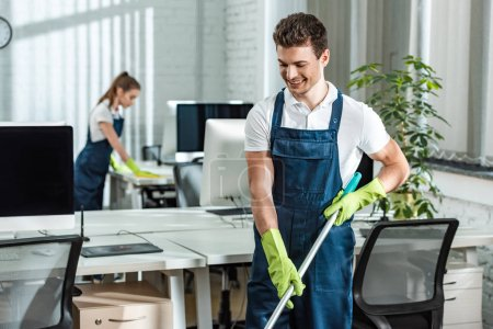 Photo for Handsome, smiling cleaner washing floor near colleague cleaning desk - Royalty Free Image
