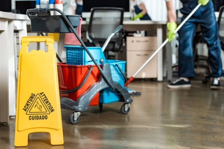 Photo for Partial view of cleaner washing floor near cart with buckets - Royalty Free Image
