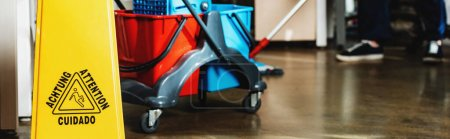cropped view of cleaner washing floor near cart with buckets, panoramic shot