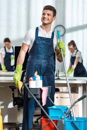 Photo for Smiling cleaner standing near cart with cleaning supplies and looking away - Royalty Free Image